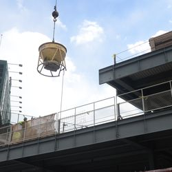 2:17 p.m. Concrete bucket being lowered on the left field bleacher patio deck -