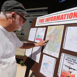 Brian Head resident Larry Cole looks over posted information as the wildfire continues to burn on Friday, June 30, 2017. Cole decided to stay in his condo while others evacuated.