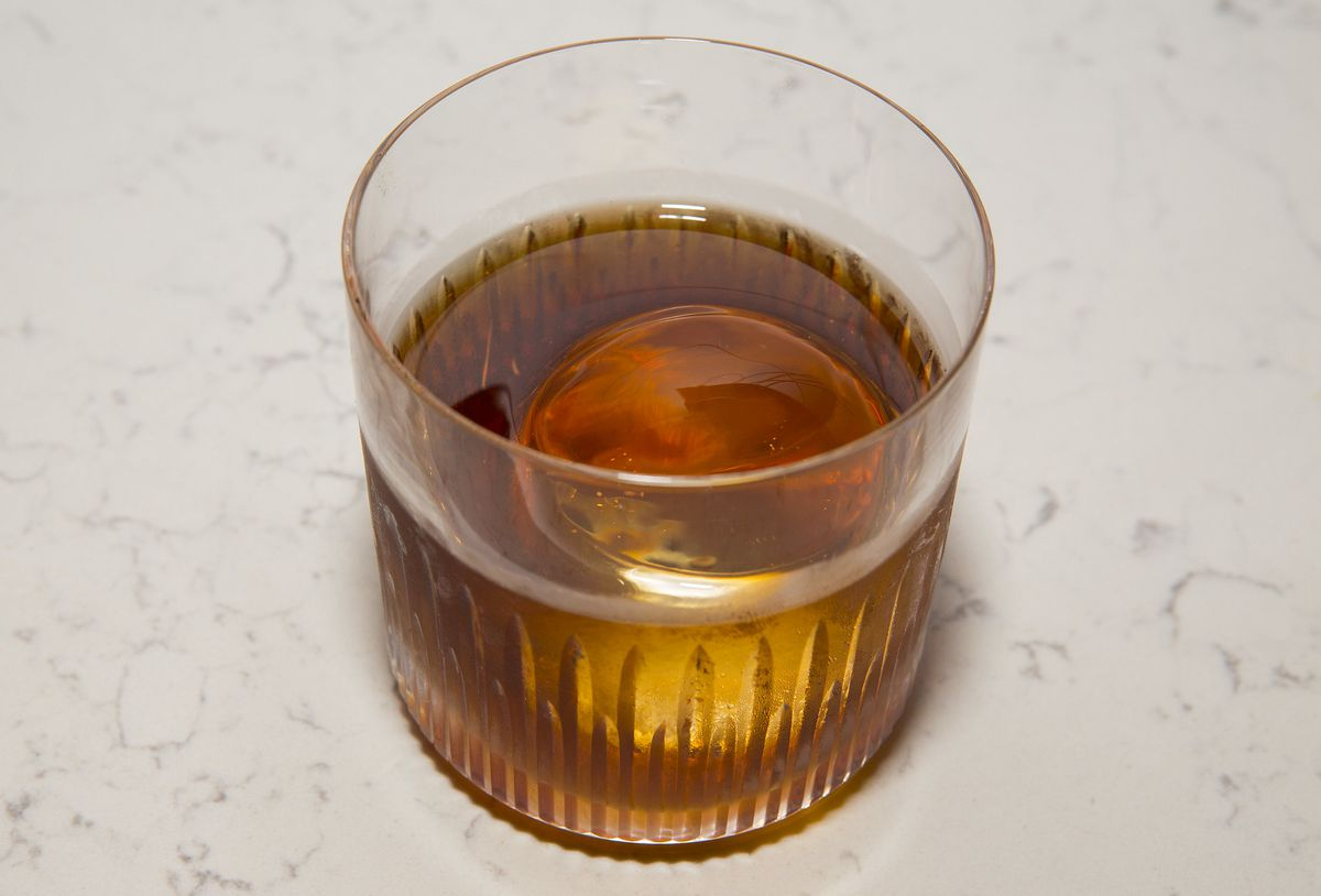 A short glass filled with a dark brown cocktail with a single spherical cube of ice.