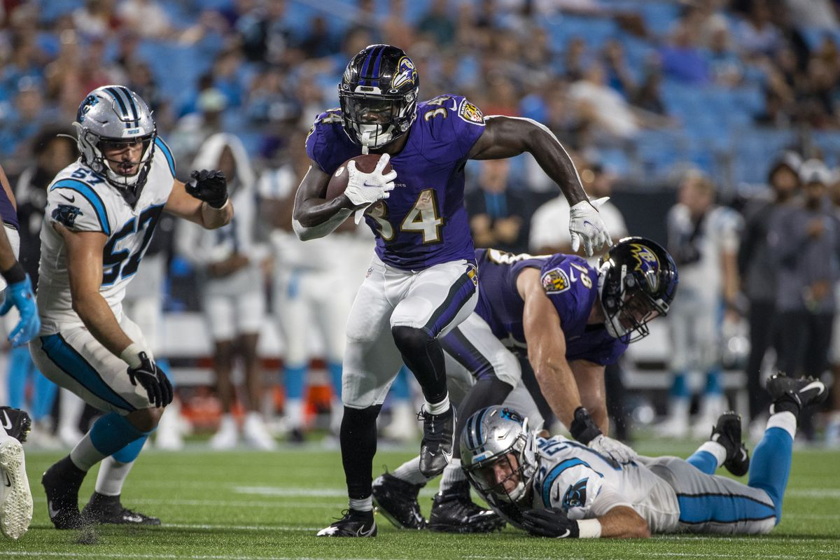 Ty'Son Williams #34 of the Baltimore Ravens runs the ball against the Carolina Panthers during the second half of a NFL preseason game at Bank of America Stadium on August 21, 2021 in Charlotte, North Carolina.
