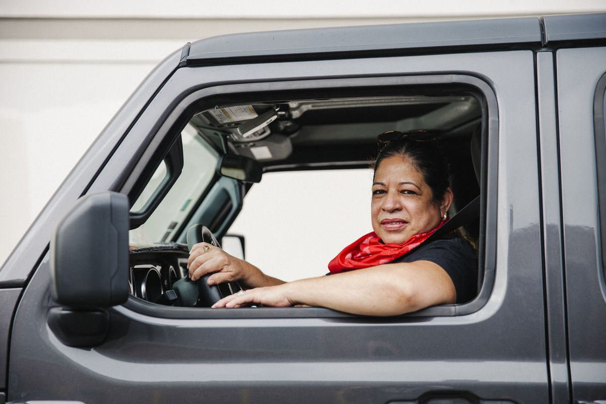 Woman wearing bandana around her neck smiles out of the window of her car.