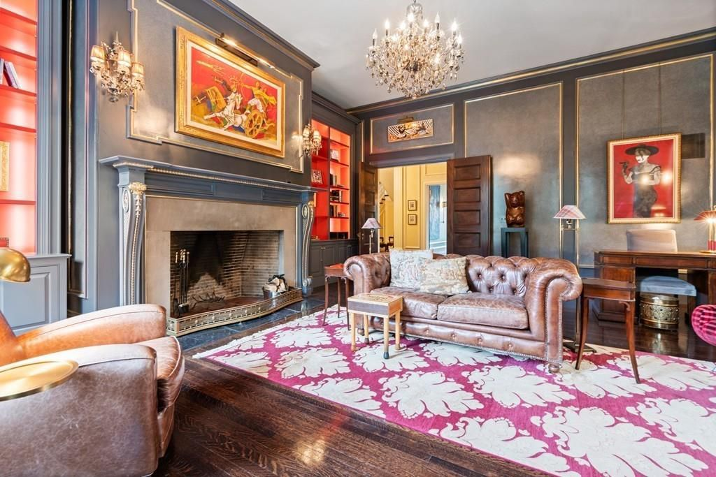 A sitting room with a couch and a chair in front of a fireplace, and there's a bright painting and a bright rug.