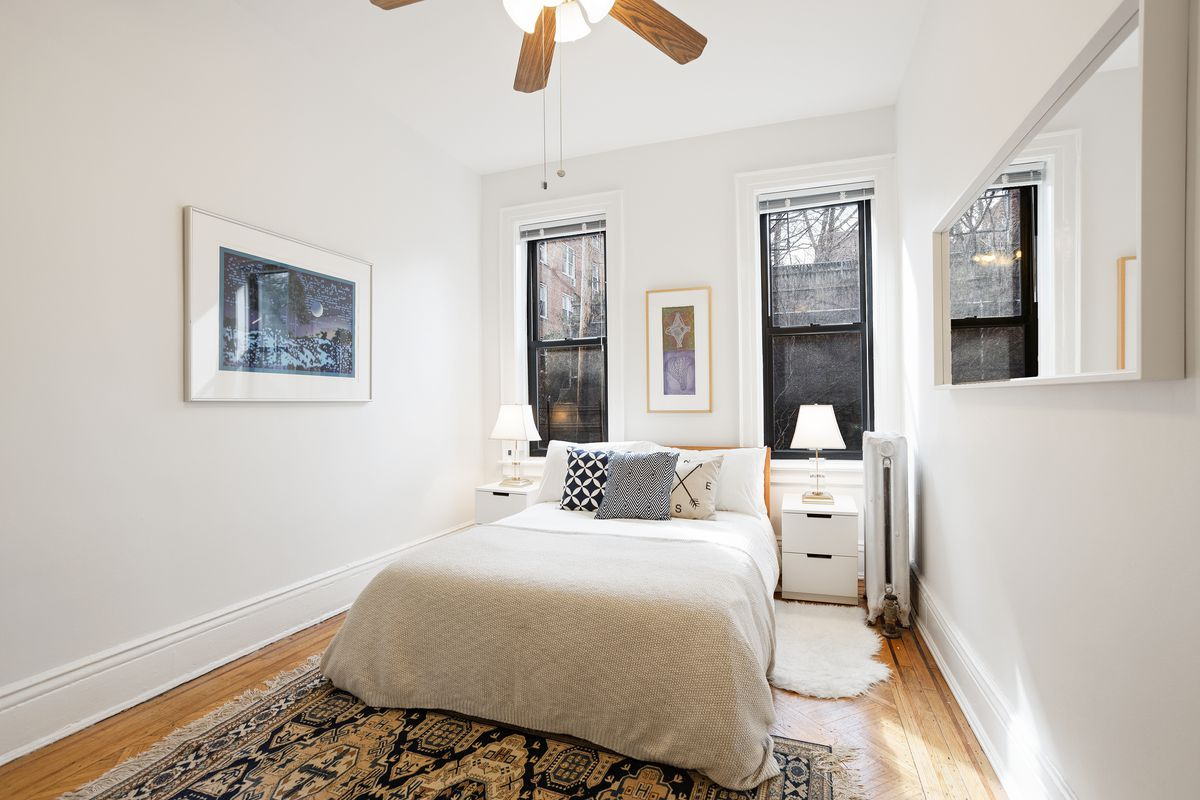 A bedroom with a small bed, two windows, a ceiling fan, hardwood floors, and a rug.