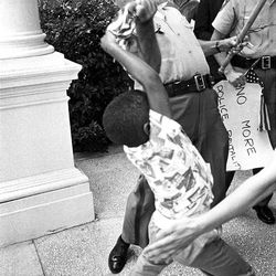 """A photo from the exhibit: Patrolman Huey Krohn tries to take a small American flag held by Anthony Quinn. Out of sight, his mother is saying, """"Anthony, don't let that man take your flag."""" When Anthony refuses to give up his flag, the patrolman goes berserk, wrenching it out of his hands. This picture was a winner in the 1965 World Press Photo Contest. Matt Herron, Jackson, Miss., 1965"""