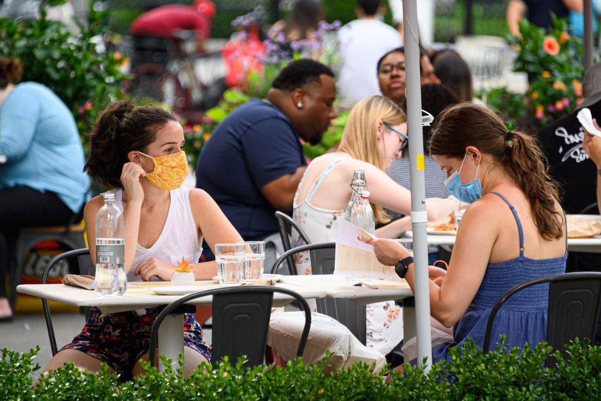 People wear protective face masks at an outdoor restaurant in the Flatiron District as the city continues Phase 4 of re-opening following restrictions imposed to slow the spread of coronavirus on July 26, 2020 in New York City.