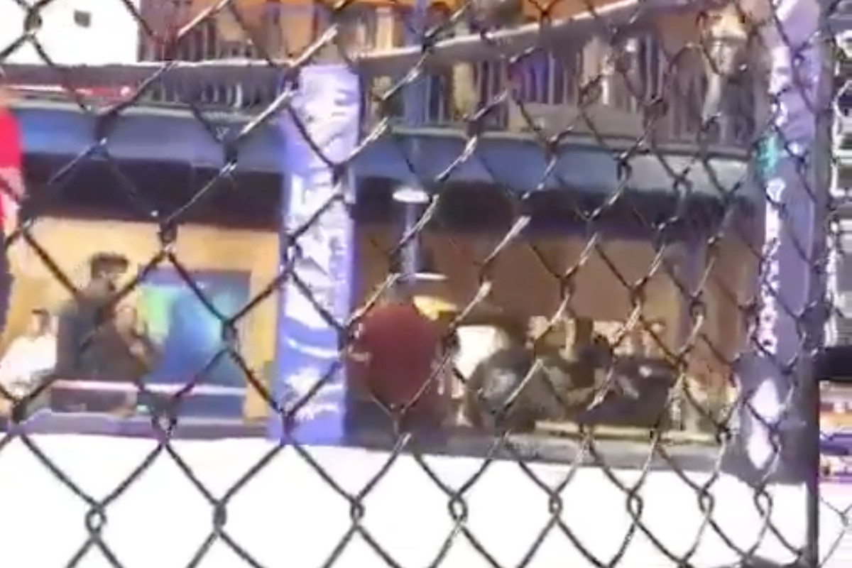 The man in red (center) indiscriminately fired his gun in the air as a brawl broke out during an MMA event in Florida on Saturday.