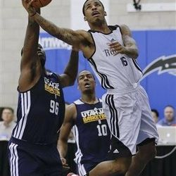 Houston Rockets' Vander Blue, right, makes a shot in front of Utah Jazz's Rick Jackson, left, during an NBA summer league basketball game, Tuesday, July 9, 2013, in Orlando, Fla. (AP Photo/John Raoux)