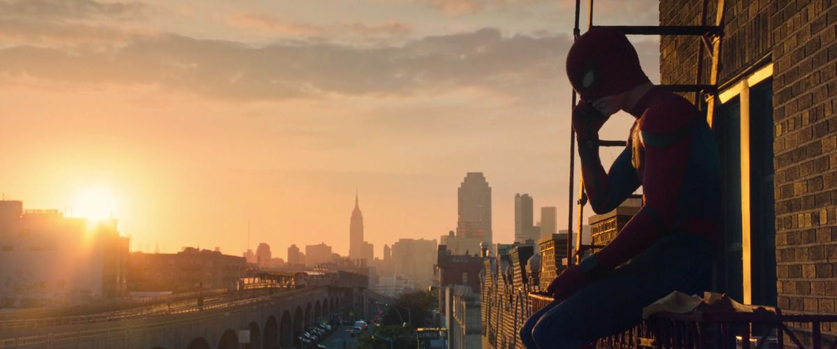 spider-man sits on the ledge of a building talking on the phone