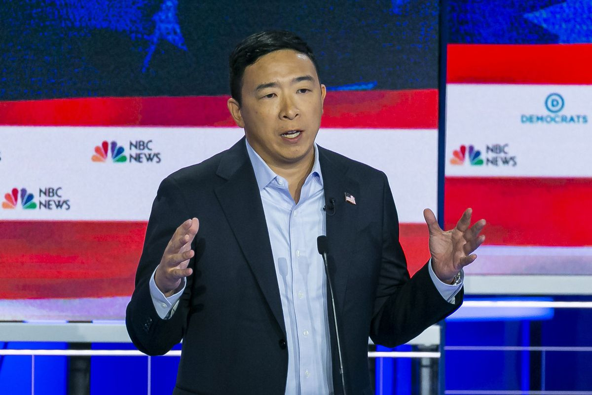 Presidential candidate Andrew Yang holds his hands out while onstage at the first Democratic debate.