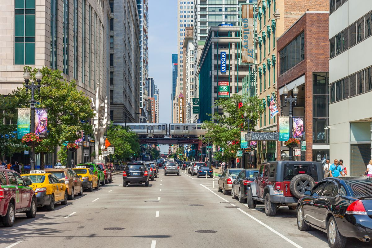 A view of cars parallel parked on a downtown street with brick buildings, bright sun, green trees, and a CTA train car passing on elevated tracks in the distance.