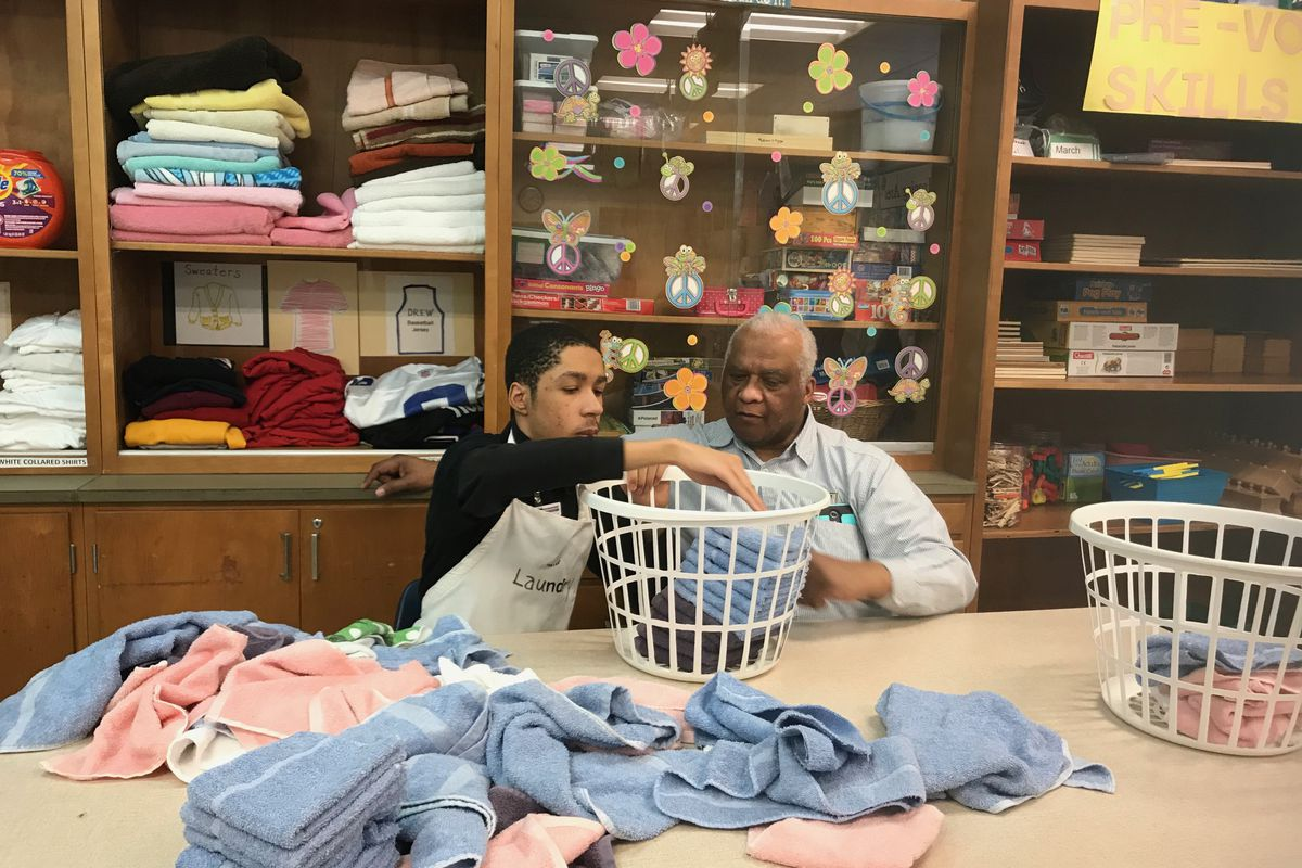 A Charles R. Drew Transition Center student practices folding laundry as his teacher looks on at the special education school in Detroit