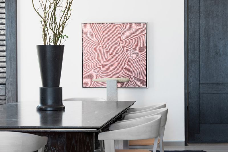 Dining room with white walls, a square-shaped art work featuring red lines, and a black table with beige chairs.