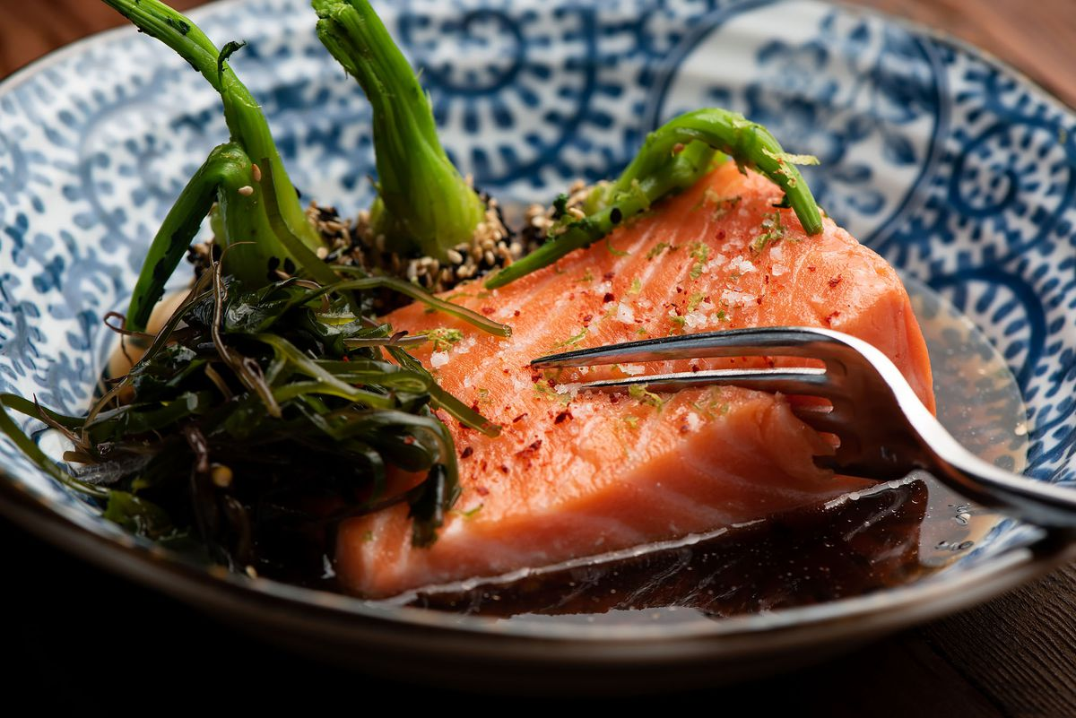 A slab of salmon with fork cutting through, sitting in bowl of dashi broth.