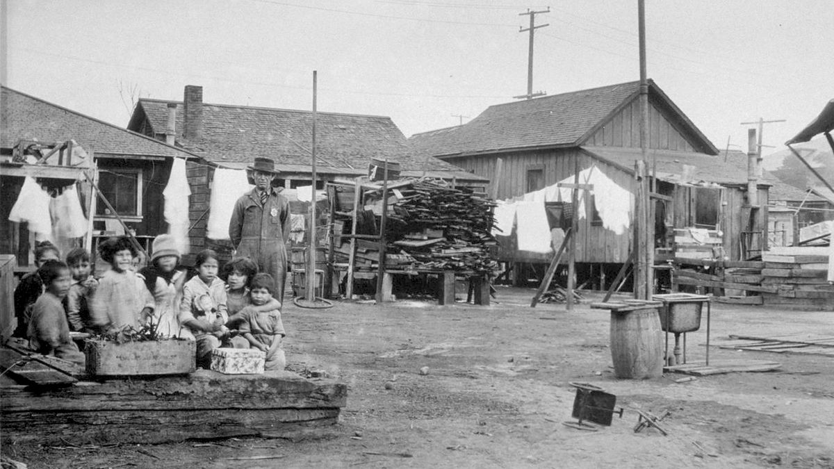 A black and white image of simple wood houses on a dirt lot. A group of children stands in front.