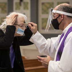 A congregant receives the imposition of ashes from Father Tom Hurley at Old St. Patrick's Catholic Church on the Near West Side on Ash Wednesday, Feb. 17, 2021. Amid fears of the coronavirus pandemic, Hurley did not touch anyone and gave out ashes on a fresh Q-tip to each congregant, then threw the Q-tip away.
