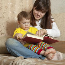 Mother showing book to her baby in home
