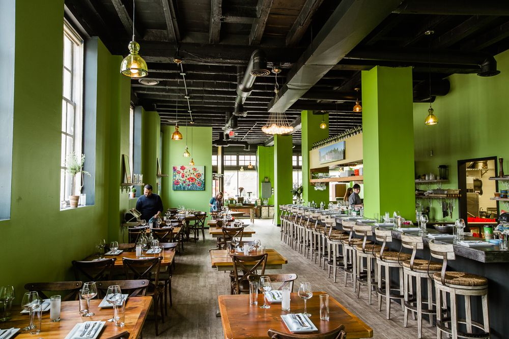 The bright green dining room at Chartreuse has sun streaming through the windows.