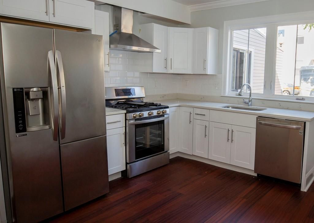 A modern kitchen with a right-angle counter and double-door fridge.