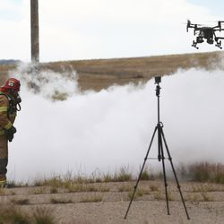 A firefighter walks through a cloud of nitrogen as a drone flies nearby during a workshop on the Goshute Skull Valley Reservation on Tuesday, June 25, 2019. The two-day workshop for emergency responders was hosted by Deseret UAS.