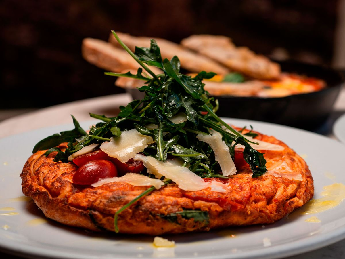 A small thick pizza on a plate topped with cherry tomatoes and greens, beside other dishes