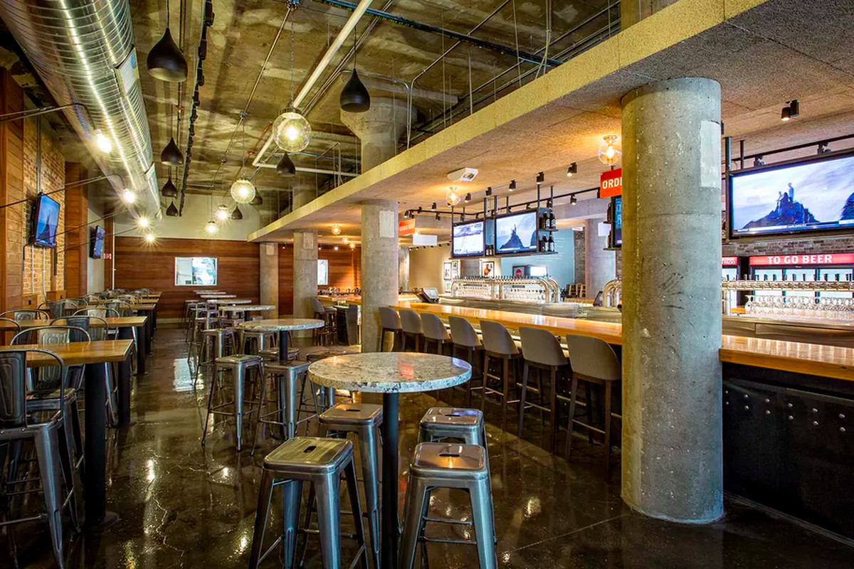 The interior of an industrial-style brewpub with tall tables and a long bar.