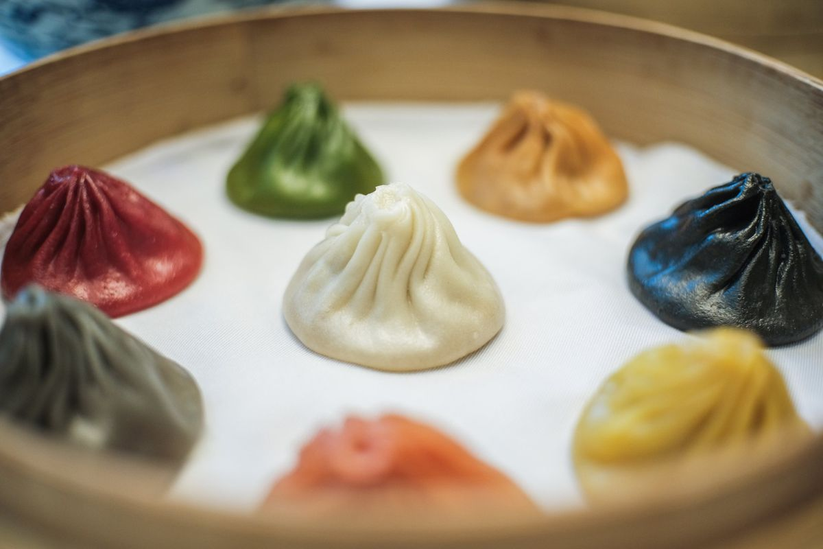 Colorful soup dumplings arranged in a bamboo steam cylinder.