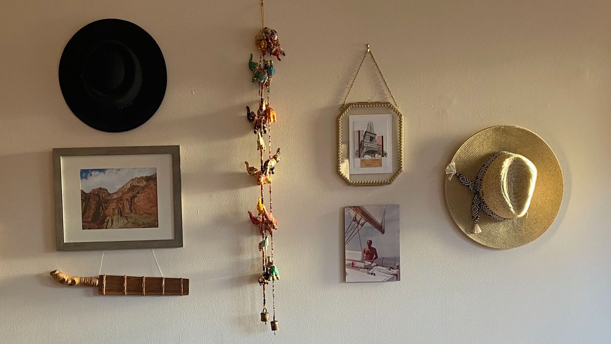 Various artworks hang on a wall, along with a hat.