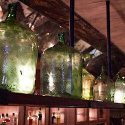 A series of vintage glass wine jugs hang over the bar