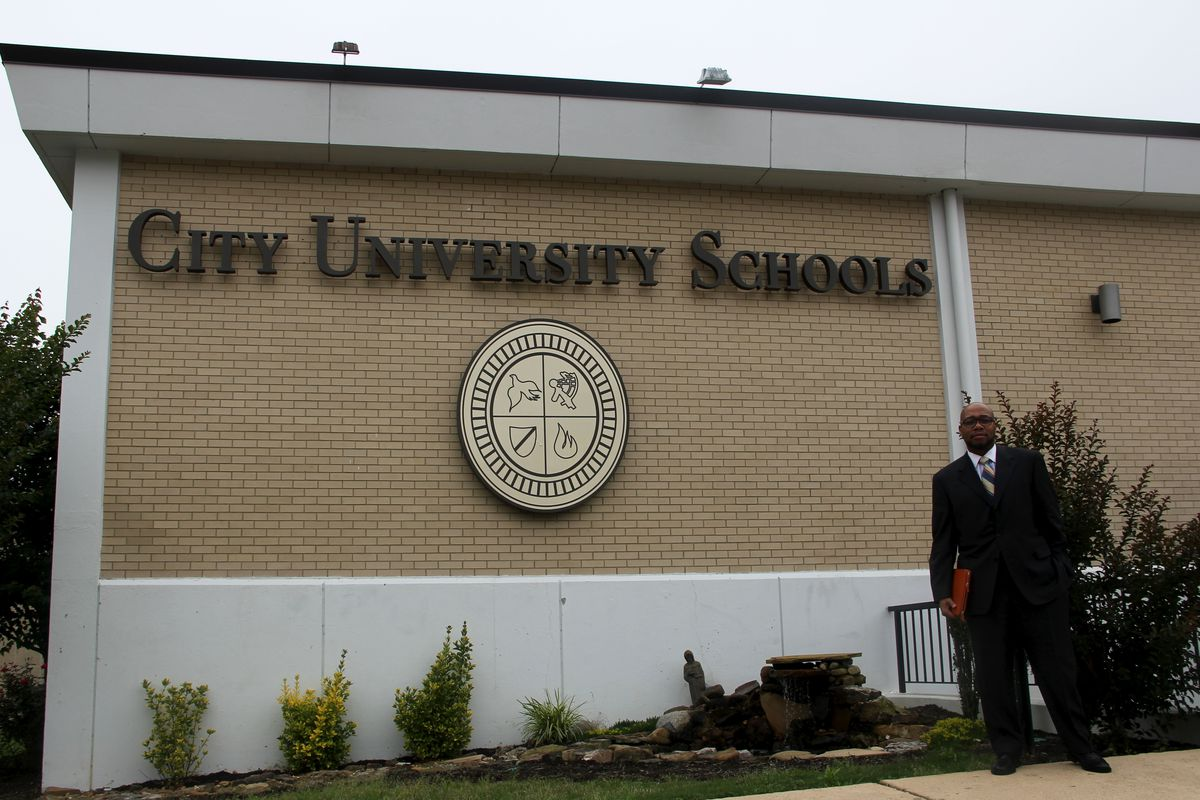 Chancellor R. Lemoyne Robinson stands outside the charter school he founded in 2004. The school will remain open next school year.