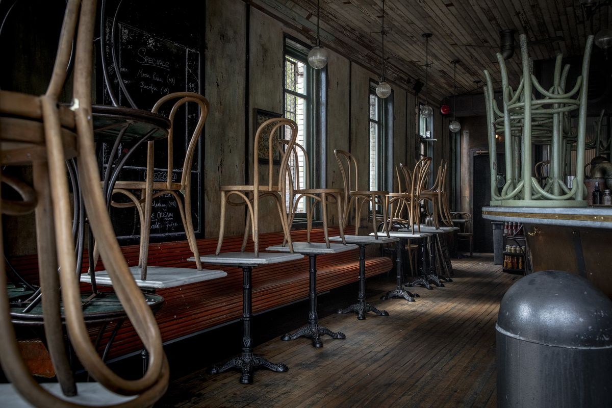 Inside an empty restaurant with the chairs stacked up on top of marble tables