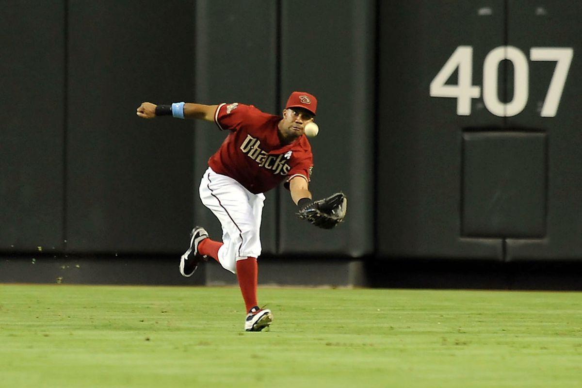 PHOENIX, AZ - JUNE 19:  Chris Young #24 of the Arizona Diamondbacks makes a running catch in the outfield against the Chicago White Sox at Chase Field in Phoenix, Arizona.  (Photo by Norm Hall/Getty Images)