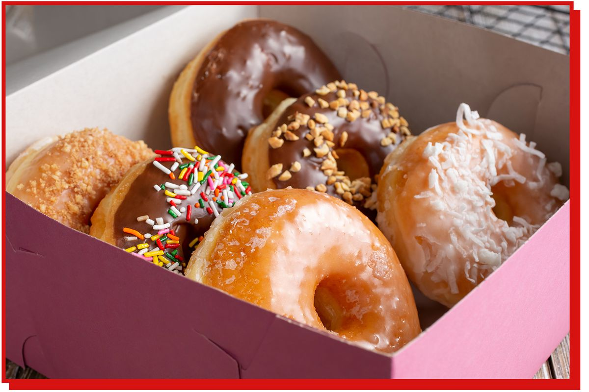Six doughnuts of different varieties inside a pink box.