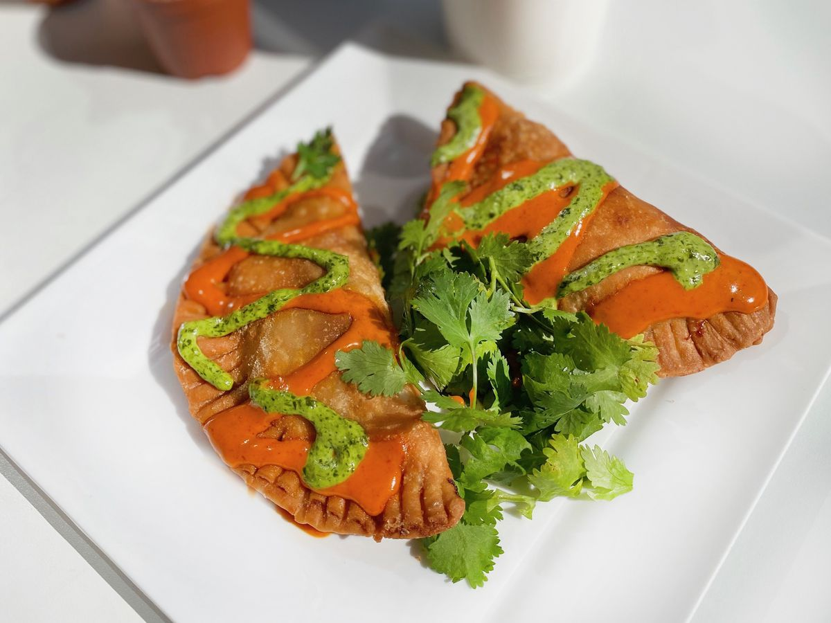 Two fried empanadas are covered in red and green sauces and accompanied by a sprig of cilantro. A cup of coffee sits in the background.