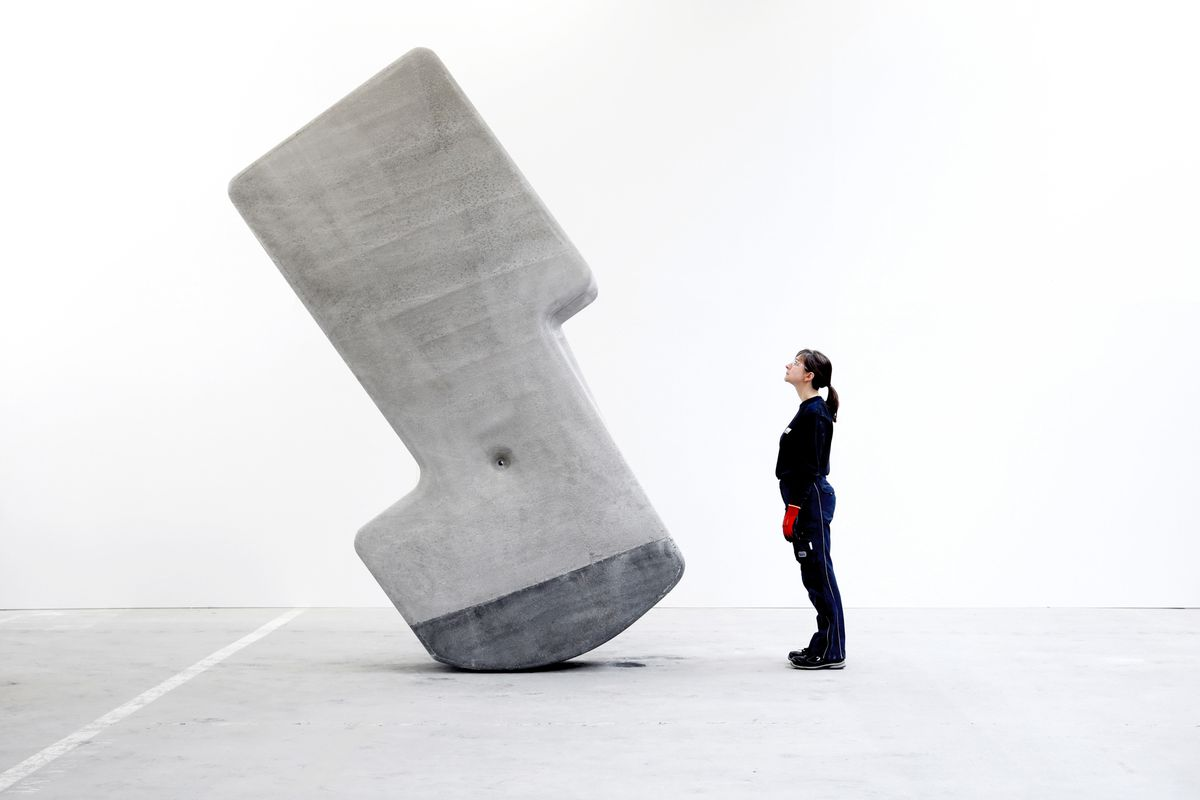 Woman standing next to leaning rock