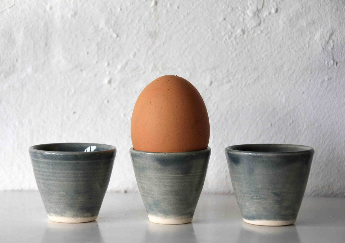 Three gray egg cups and one egg