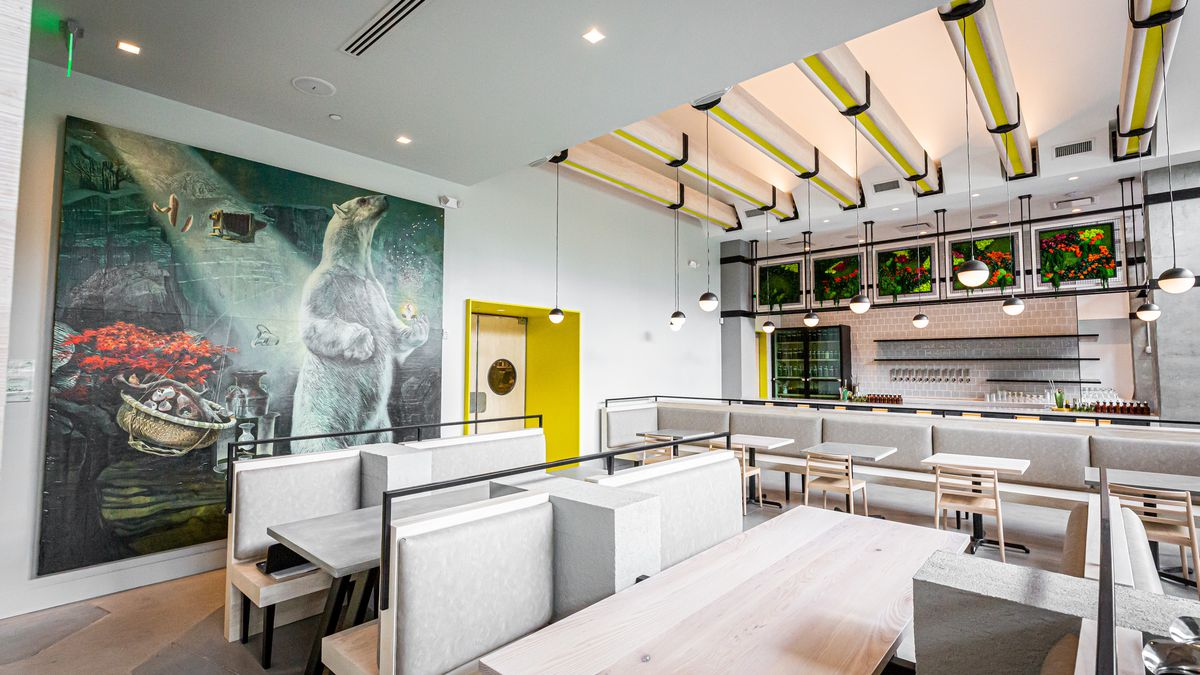 Looking toward the bar in the dining room at Cold Beer with the polar bear portrait next to the yellow kitchen doors, two booths, and banquette and tables in the background