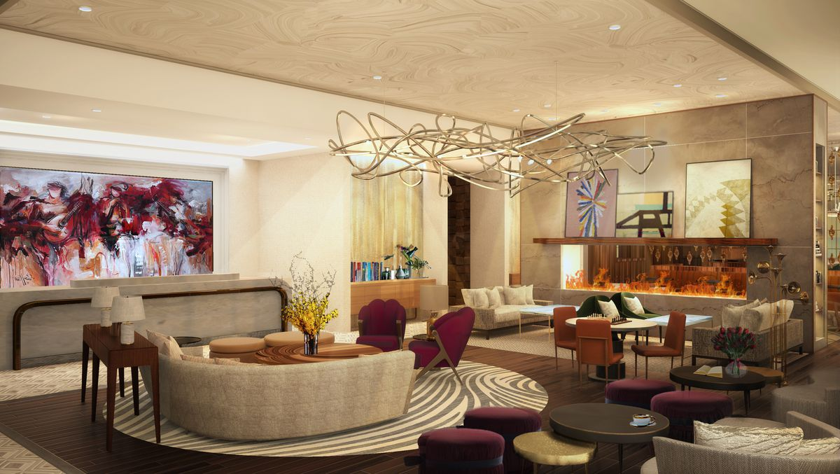 A hotel lounge with a modern look, with curved furniture and a wired light fixture from the ceiling.