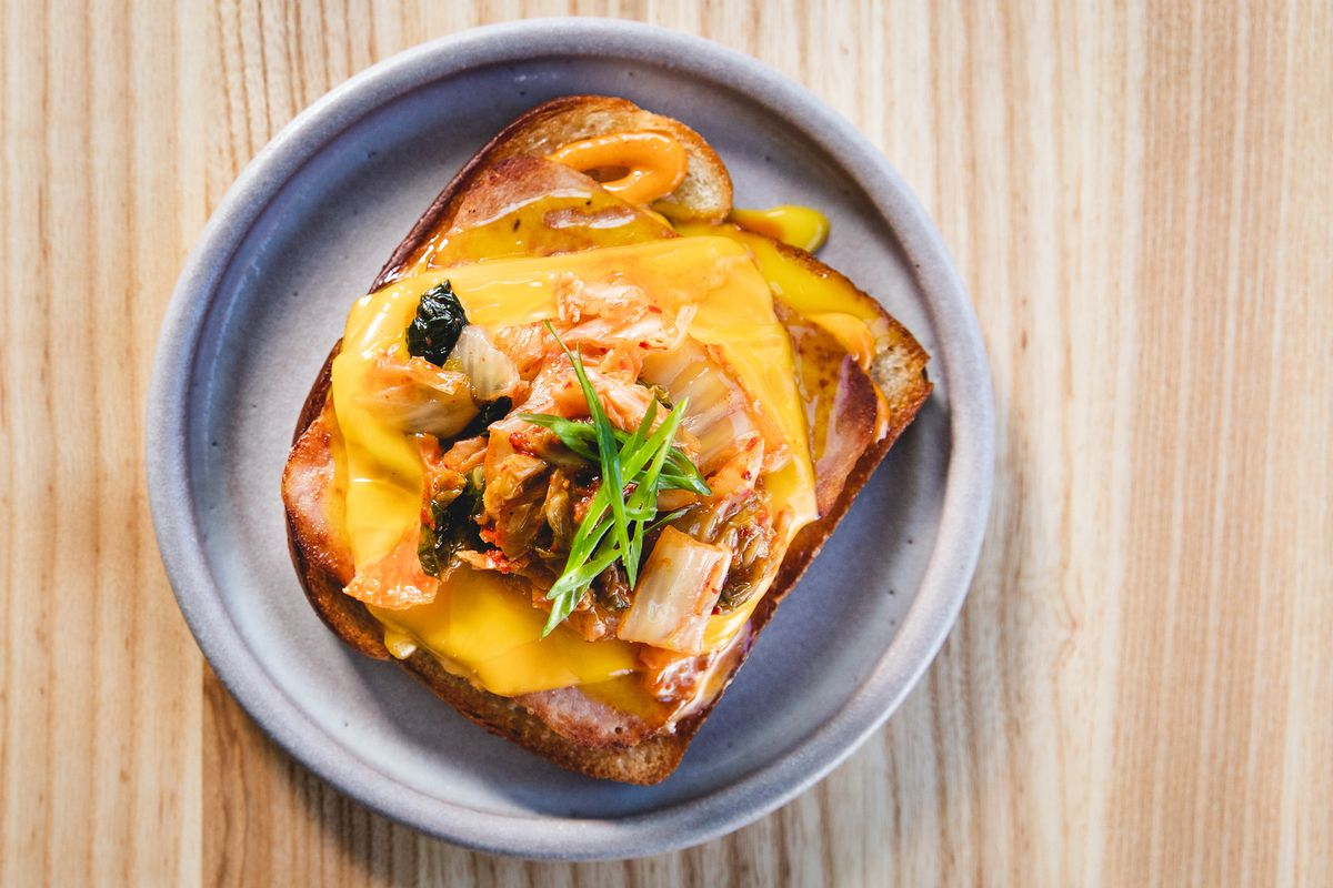 A piece of bread topped with yellow American cheese and a pile of kimchi.