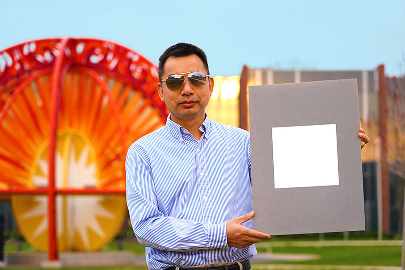 A man with sunglasses on holding up a panel with a very bright white square painted on it.