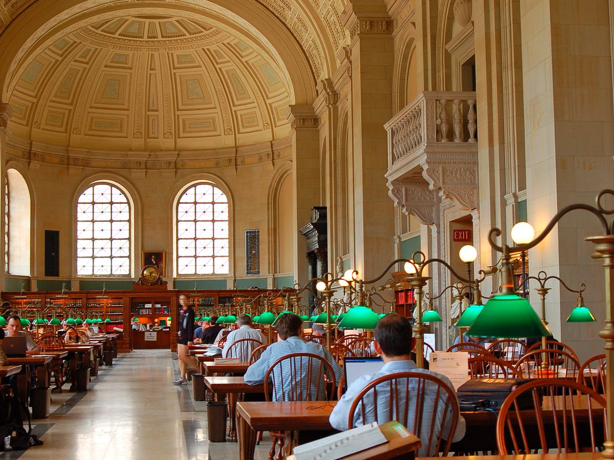 A cavernous reading room in a library, and people reading in it at rows of tables.
