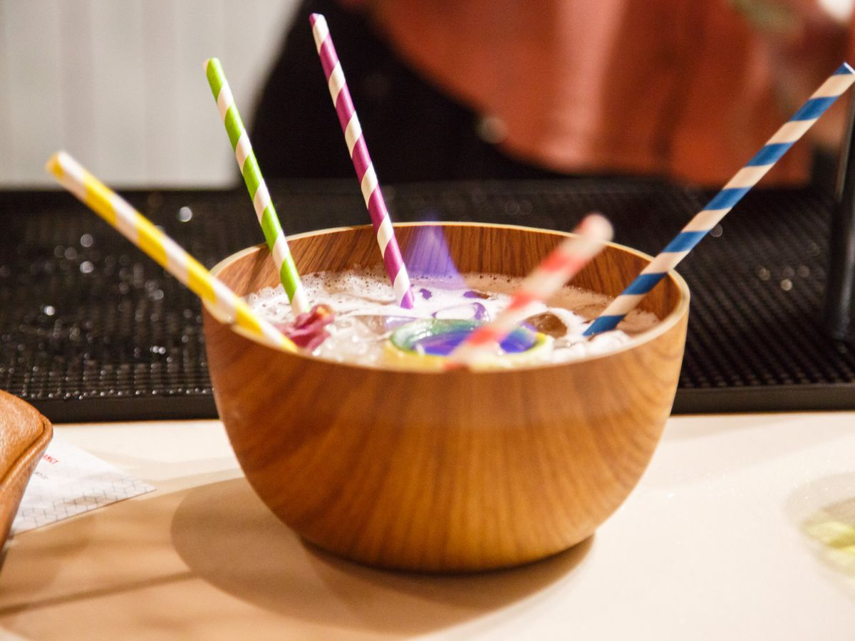 A large wooden bowl is full of booze, with a flame coming out of the top. There are five straws with different colored stripes in it.