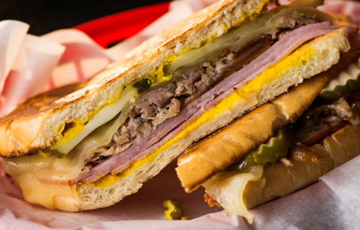 A closeup of a Cuban sandwich, with ham, roast pork, pickles, and mustard.