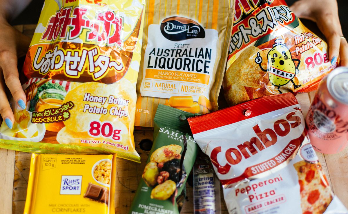Calbee honey butter potato chips, soft Australian licorice, Calbee hot and spicy chips, pepperoni pizza Combos, Sahale pistachios, Ritter Sport chocolate laid out on a table.