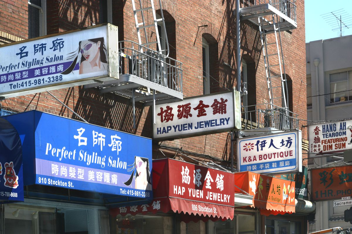 Signs hang over the entrances to a variety of small businesses in Chinatown.