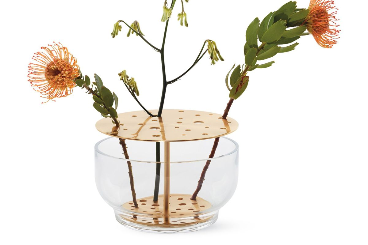 Broad-bottomed glass vase with wide mouth and brass stand for holding flowers.