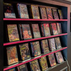 Adult films line this bookcase found near the bathrooms.