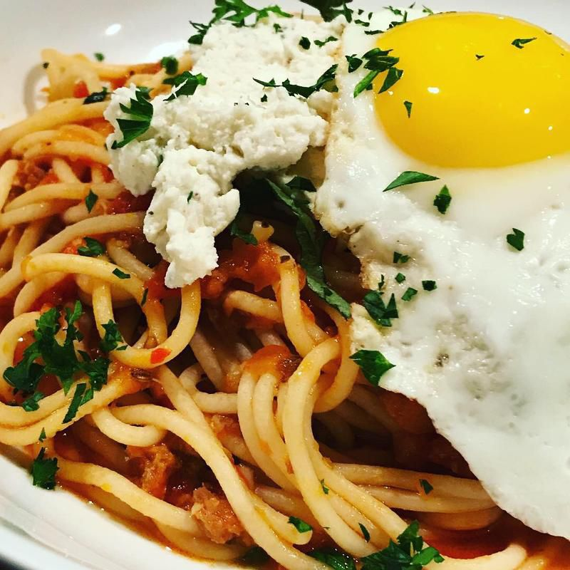 Breakfast spaghetti served with sausage, ricotta, and a sunny egg