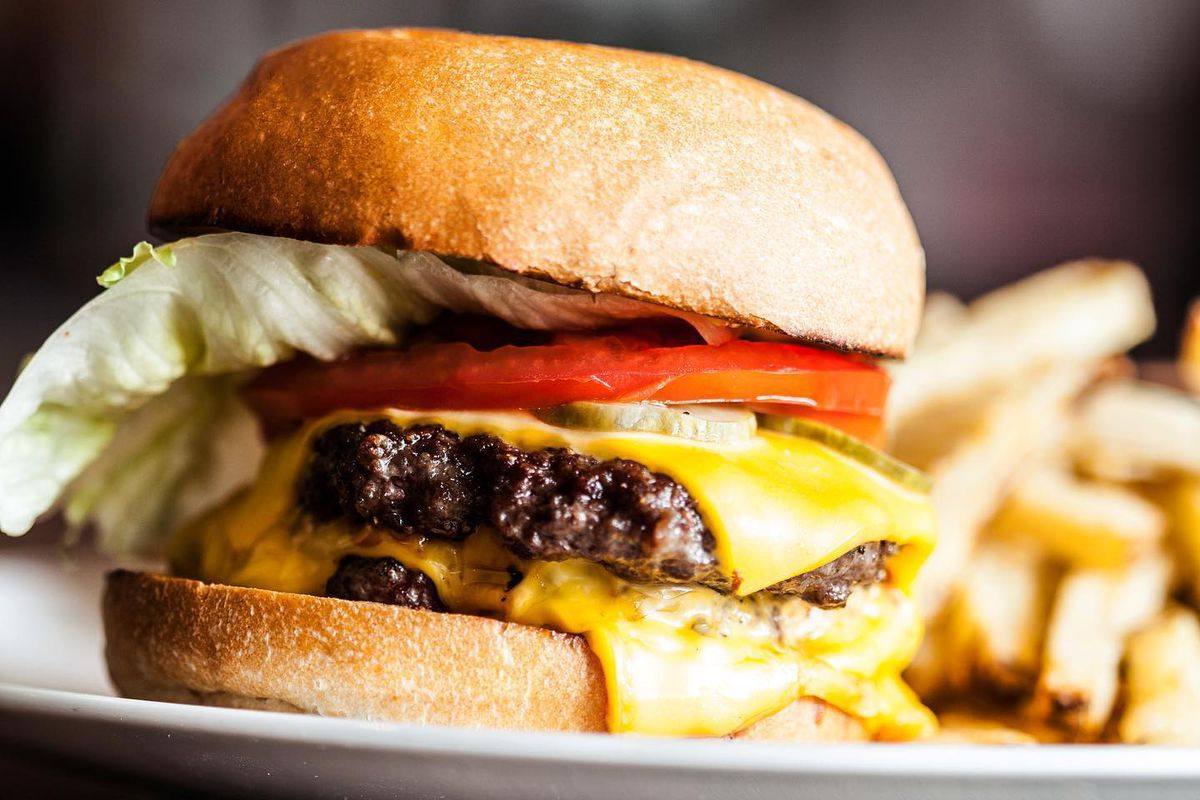 A cheeseburger topped with tomato, lettuce, two burger patties, and cheese. Fries sit in the background.