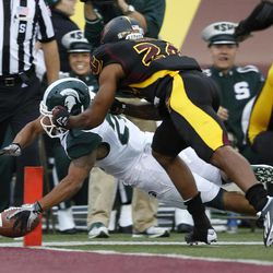 Michigan State's Nick Hill, left, dives into the end zone against Central Michigan's Leron Eaddy (24) during the fourth quarter of an NCAA college football game on Saturday, Sept. 8, 2012, in Mount Pleasant, Mich. The play was called back due to a penalty but Hill scored later in the series. Michigan State won 41-7.