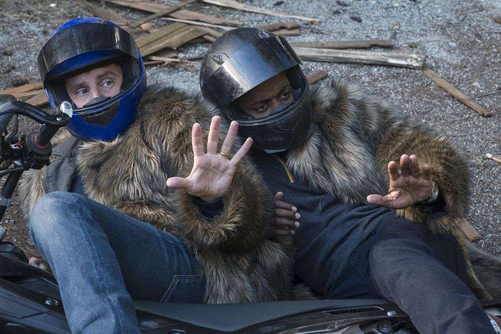 shawn and gus in motorcycle helmets and fur coats, on the ground